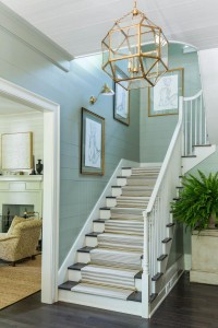 An elegant staircase extends the foyer, and shiplap and gold finishes accent the design.