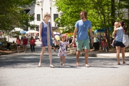 A family soaks up the sun in Mt Laurel's town center during the annual Spring Festival.