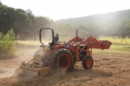 A farmer stirs up dust as he prepares the land for new crops.