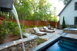 This backyard oasis includes a dipping pool, hot tub, and two comfortable chaise lounge chairs.