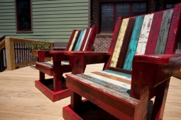 A wide back porch deck offers plenty of space for these colorful lounge chairs.