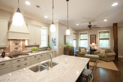 Marble countertops and pendant light fixtures beautifully accent this kitchen/living room space.