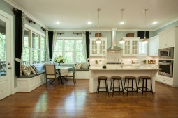 This open kitchen flows into the breakfast area highlighted by banquette seating surrounded by windows overlooking the trees.