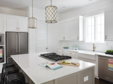 Quartz counters, antique gold finishes, shiplap walls, and a farmhouse kitchen sink complete a contemporary clean design in this kitchen.  Photo: Tommy Daspit