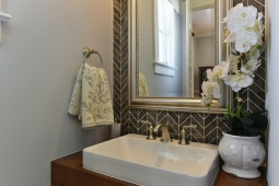 Herringbone tile and wood vanity creates a beautiful contemporary design in this hall bathroom.