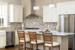 Beautiful kitchen with quartz counters, farmhouse sink, tile backsplash, and Kitchenaid appliances.